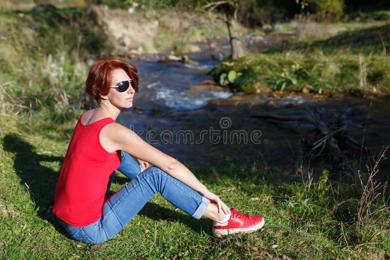 Junge Frau in der Sonnenbrille sitzt auf dem grünen Gras nahe einem Strom an einem sonnigen Herbsttag stockfotografie