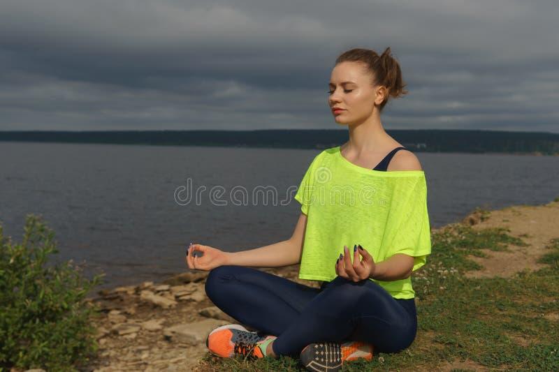 Junge Frau in der Sportkleidung, die auf Flussufer sitzt stockfotografie
