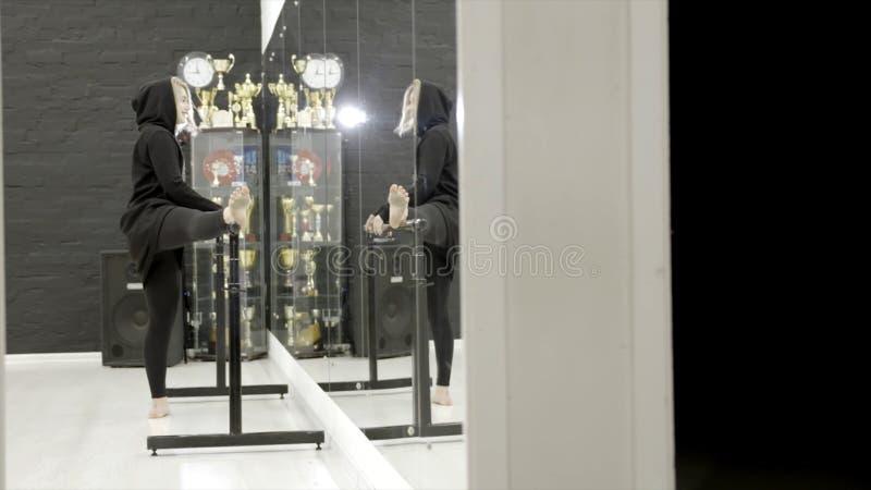 Junge Frau in der Sportkleidung, die das Ausdehnen in Turnhalle vor Spiegel tut t?tigkeit Unbeholfen sehend Handeln der jungen Fr lizenzfreie stockbilder