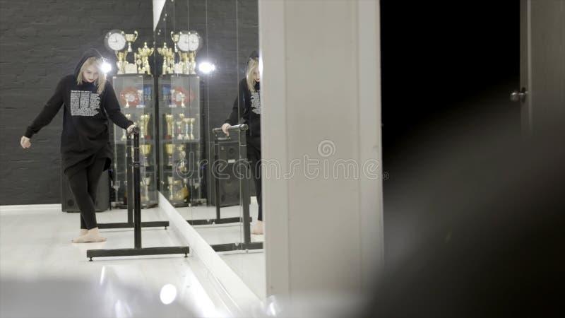 Junge Frau in der Sportkleidung, die das Ausdehnen in Turnhalle vor Spiegel tut t?tigkeit Unbeholfen sehend Handeln der jungen Fr stockbilder