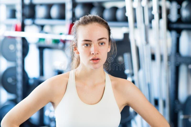 Junge Frau in der Turnhalle, im weißen Trägershirt, stehend still stockfotos