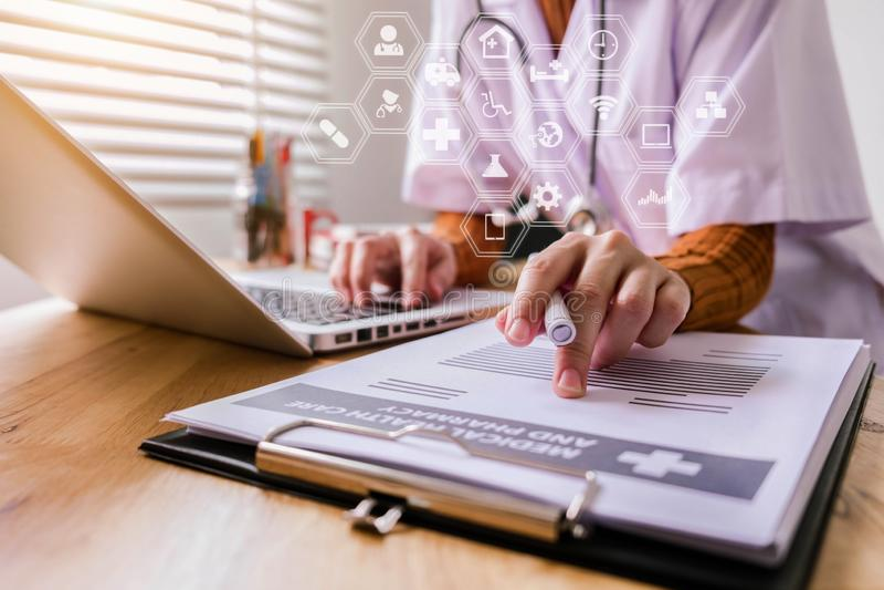 Junge Frau in der Uniform von Doktor unter Verwendung des Digitaltechniklaptops für Ausgabegerät und das Schreiben eines geduldig stockfotografie