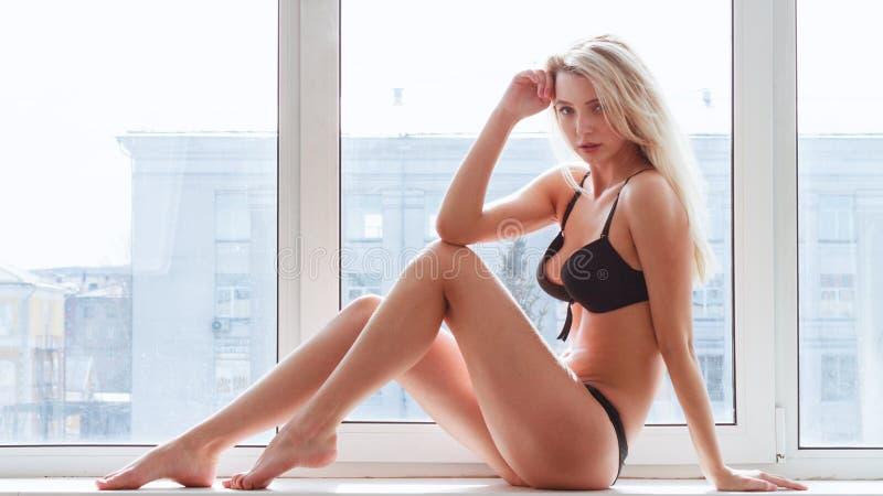 Junge Frau in der Unterwäsche, die auf Fensterbrett sitzt stockbilder