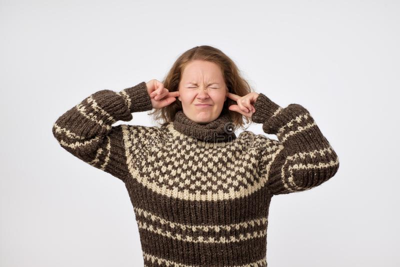Junge Frau in der warmen braunen Strickjacke, die ihre Ohren verstopft und ihr Gesicht gestört wird mit Geräuschen die Stirn runz stockbild