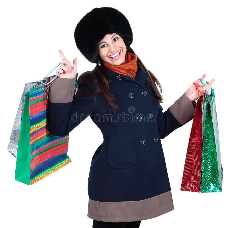 Junge Frau in der Winterkleidung mit Einkaufstaschen stockfotografie