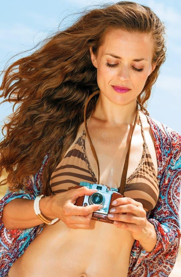 Junge Frau der Zigeunerart auf Strand unter Verwendung der Retro- Fotokamera lizenzfreie stockfotos