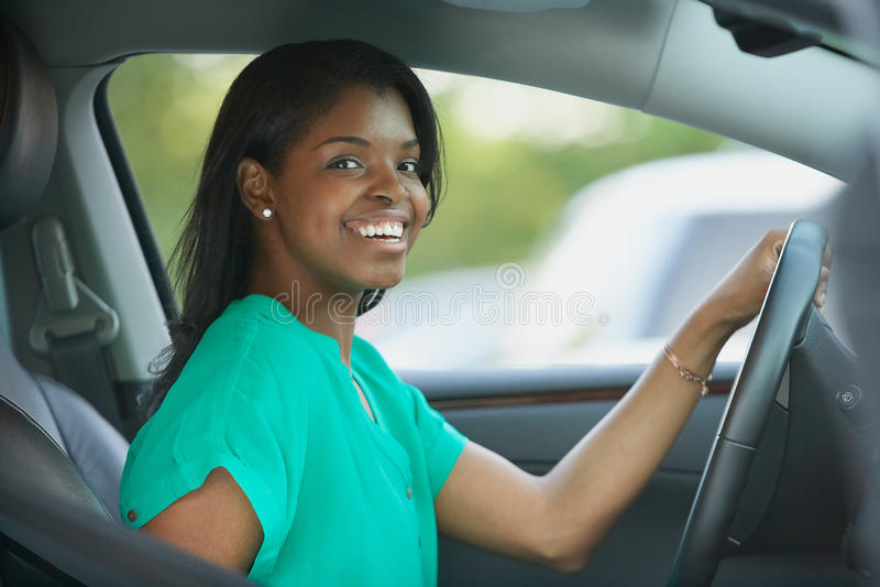 Junge Frau des Afroamerikaners im Auto lizenzfreie stockbilder