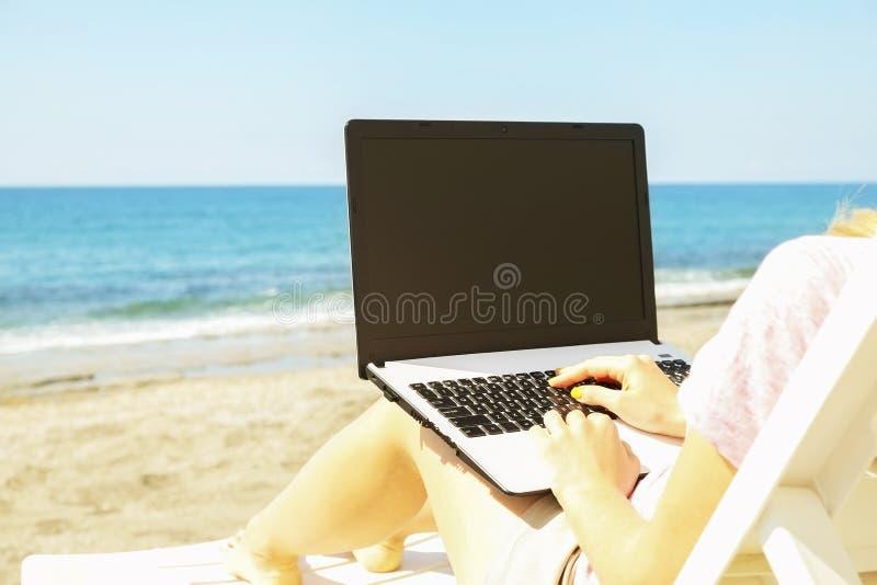 Junge Frau des blonden Haares, die an Laptop am Strand am sonnigen Tag arbeitet Schließen Sie oben von den weiblichen Händen, die lizenzfreie stockfotografie