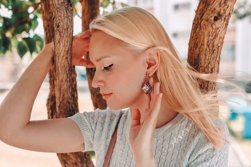 Junge Frau des blonden Haares zeigt schöne Ohrringe lizenzfreie stockbilder