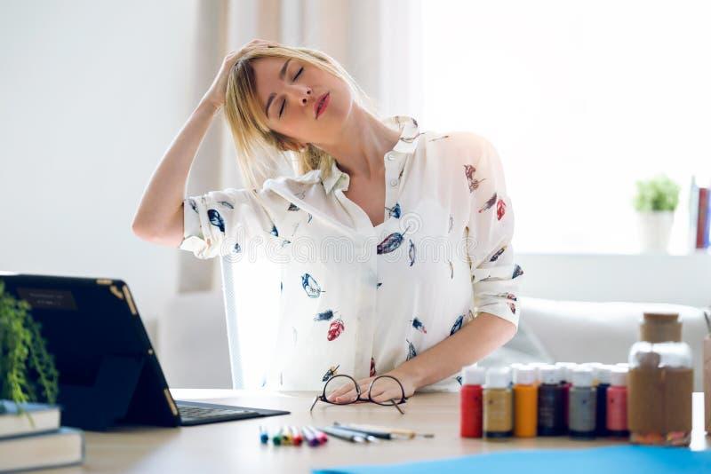 Junge Frau des Geschäfts, die Körper für die Entspannung beim Arbeiten mit digitaler Tablette im Büro ausdehnt lizenzfreie stockfotografie