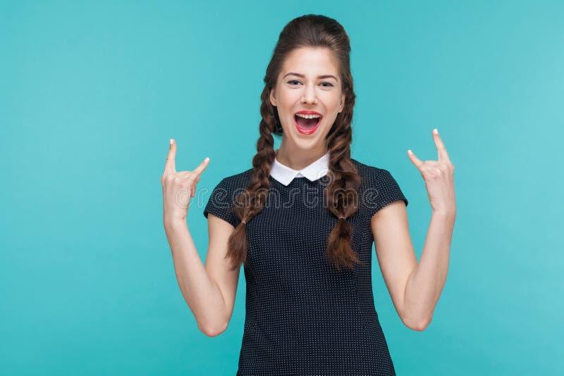 Junge Frau des Glückes, die Rock-and-Rollzeichen zeigt stockfotos