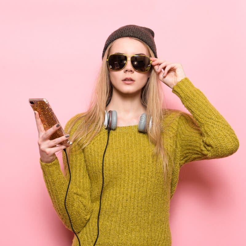 Junge Frau des Hippies, die Handy verwendet und Musik vorwählt, um auf Kopfhörern zu hören stockfoto