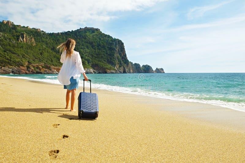 Junge Frau des Hippies im Urlaub im Jeanskleid, weißes Baumwollhemd ombre Haar, das zum Meer mit Koffer am perfekten sonnigen Tag stockfoto