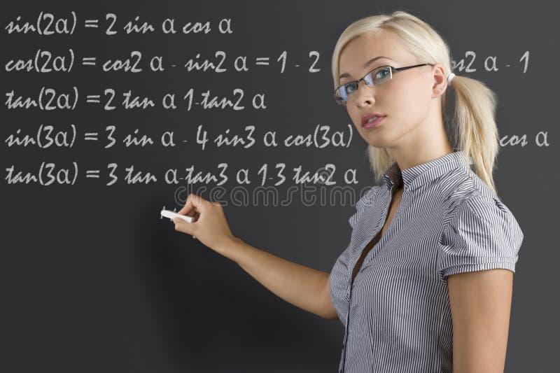 Junge Frau des Lehrers an der Tafel stockfotos