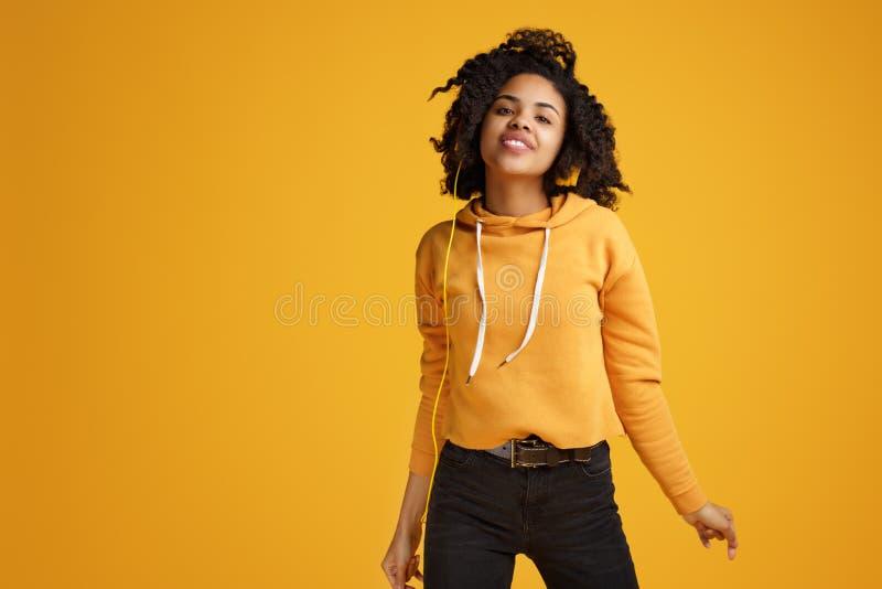 Junge Frau des modischen Afroamerikaners mit hellem L?cheln gekleidet in h?render Musik der Kleidungs der zuf?lligen Kleidung und lizenzfreie stockfotos