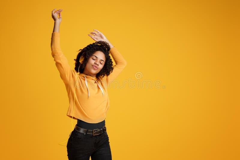 Junge Frau des modischen Afroamerikaners mit hellem L?cheln gekleidet in h?render Musik der Kleidungs der zuf?lligen Kleidung und stockfoto