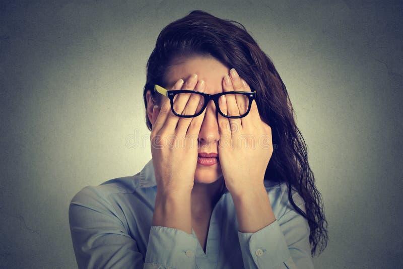 Junge Frau des Porträts in den Gläsern, die Gesicht bedecken, mustert unter Verwendung ihrer beider Hände stockfoto