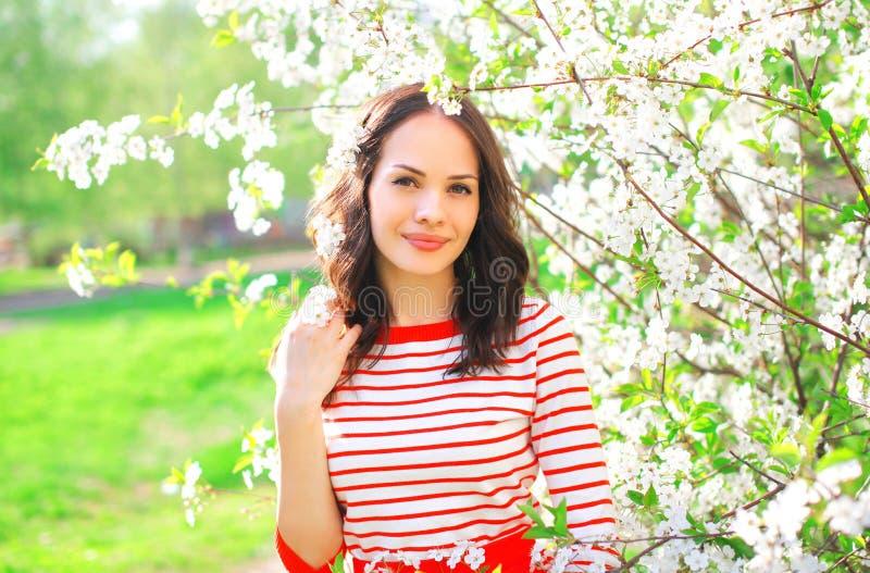 Junge Frau des Porträts recht über Frühlingsblumen lizenzfreie stockbilder