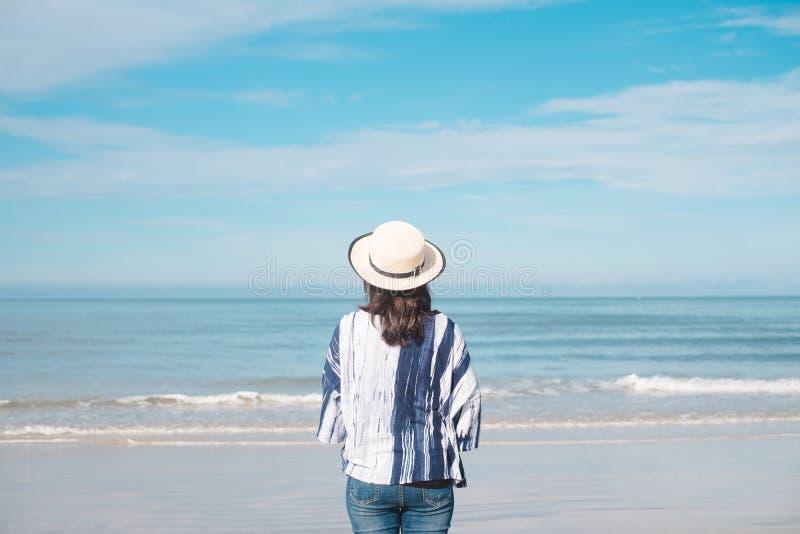 Junge Frau des Reisenden in der legeren Kleidung mit Hutstand allein auf bea stockfotografie