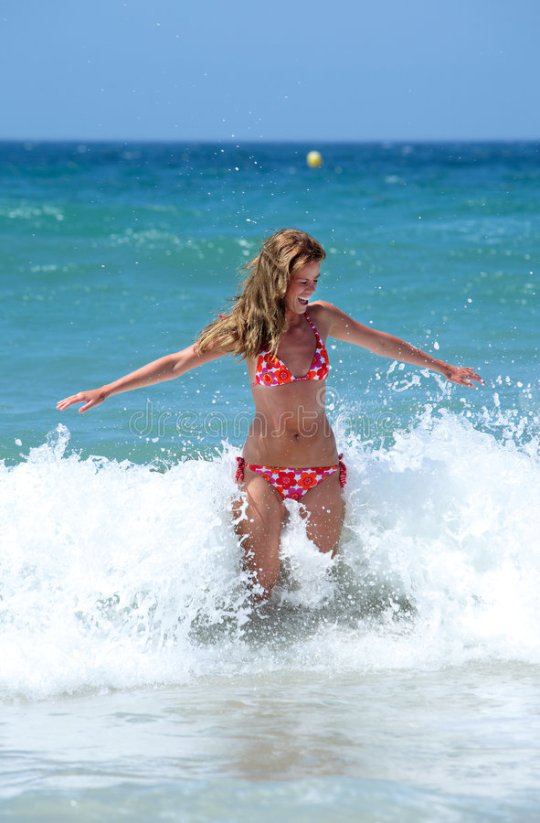 Junge Frau des reizvollen Pass-Sitzes, die durch eine Welle gespritzt wird lizenzfreies stockfoto