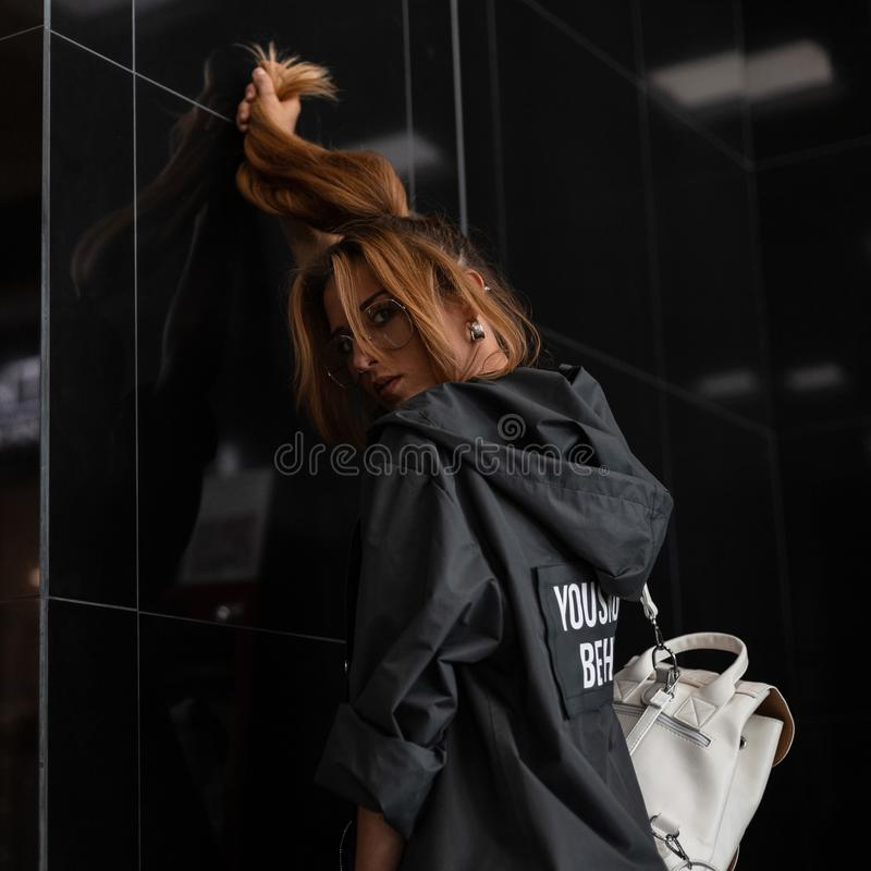Junge Frau des rothaarigen modernen Hippies in der modischen Kleidung in den stilvollen Gläsern mit einem Rucksack ist, halten st stockfotos