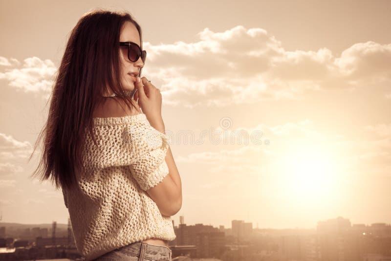 Junge Frau des schönen Brunette, die über Sonnenuntergangstadthintergrund aufwirft lizenzfreies stockbild