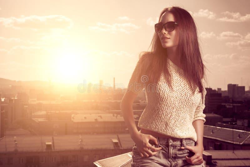 Junge Frau des schönen Brunette, die über Sonnenuntergangstadthintergrund aufwirft stockbild
