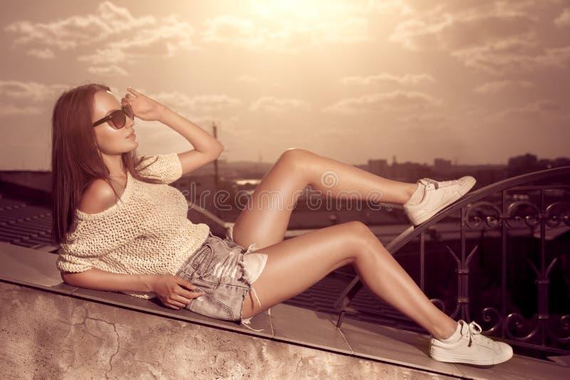 Junge Frau des schönen Brunette, die über Sonnenuntergangstadthintergrund aufwirft stockfotografie