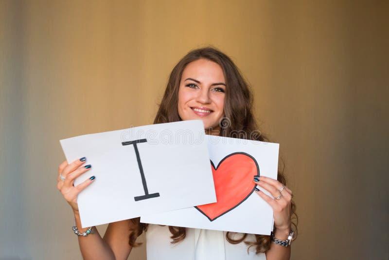 Junge Frau des schönen Brunette, die in ihren Händen zwei Frieden hält lizenzfreies stockfoto