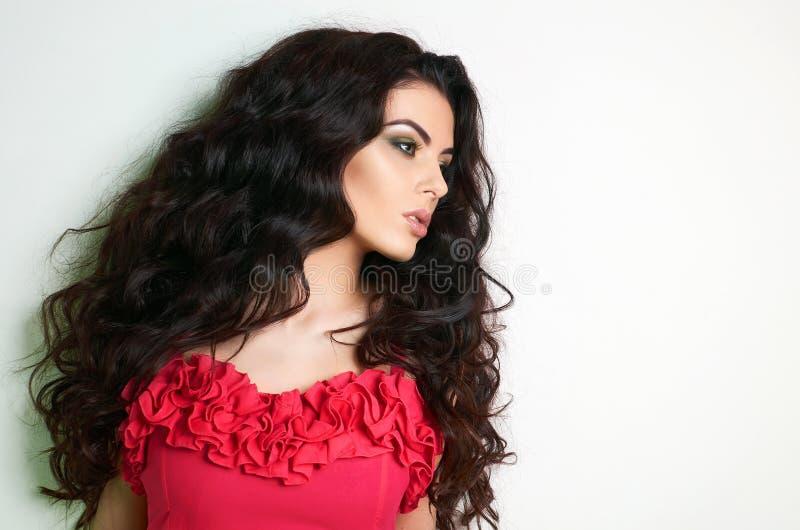 Junge Frau des schönen Brunette im roten Kleid stockbild