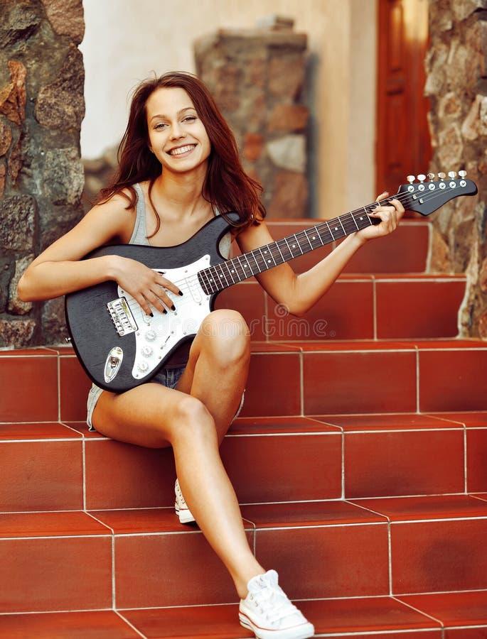 Junge Frau des schönen Brunette mit der Gitarre, die auf Treppe sitzt stockbilder