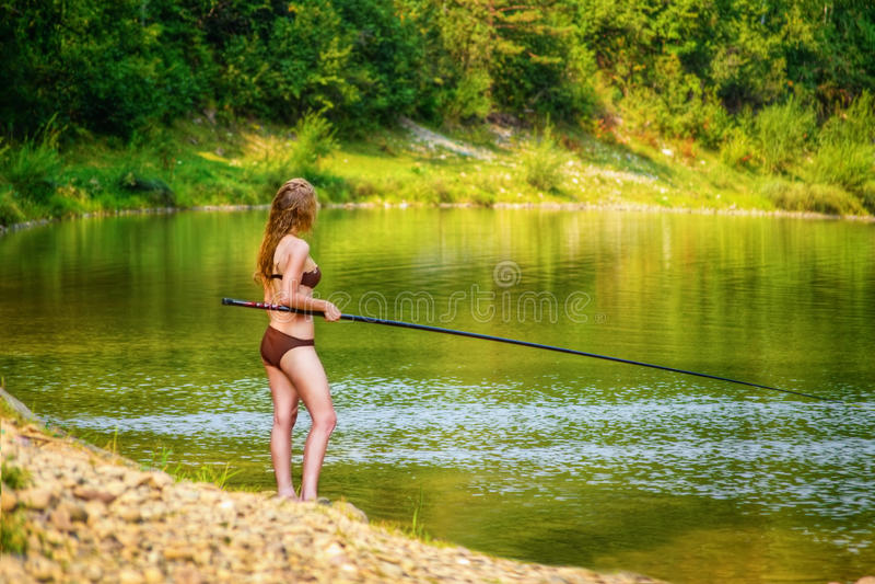 Junge Frau des schönen Fischens lizenzfreie stockbilder