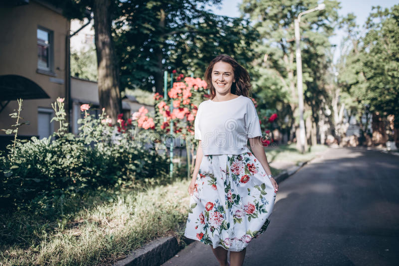 Junge Frau des schönen sinnlichen Brunette in der weißen Bluse und Rock mit Blumen gehen auf die Straße nah an rotem Rosenbusch lizenzfreies stockfoto
