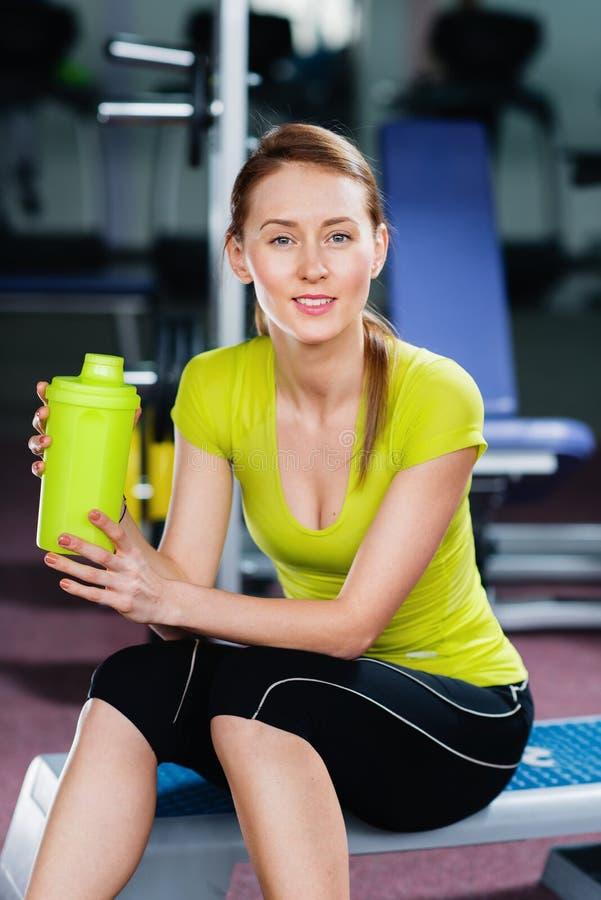 Junge Frau des schönen Sitzes mit Flasche Wasser in ihren Händen stockfoto