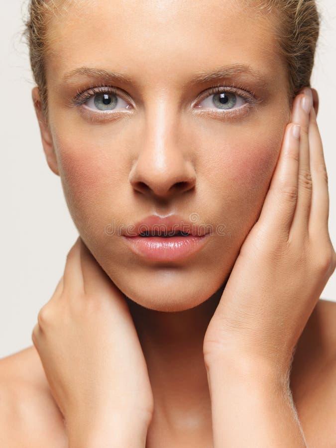 Junge Frau des Schönheitsportraits, die ihr Gesicht berührt lizenzfreie stockfotos