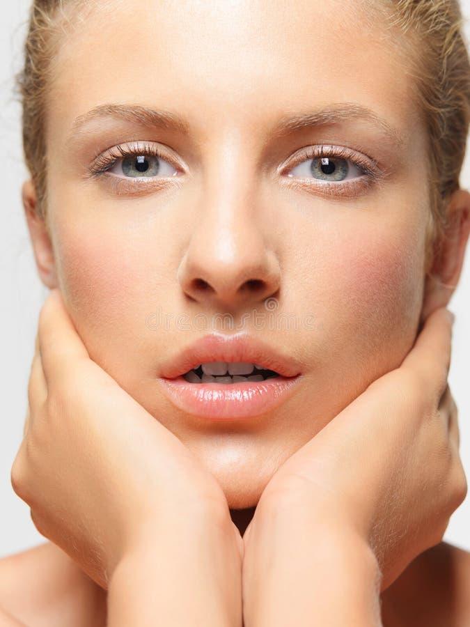 Junge Frau des Schönheitsportraits, die ihr Gesicht berührt lizenzfreies stockbild