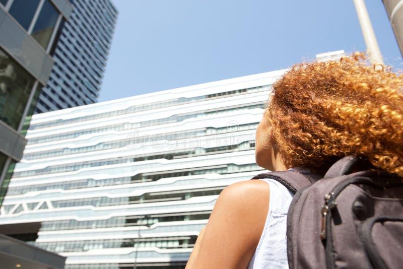 Junge Frau des Seitenporträts mit Tasche oben gehend und Gebäuden betrachtend stockfoto