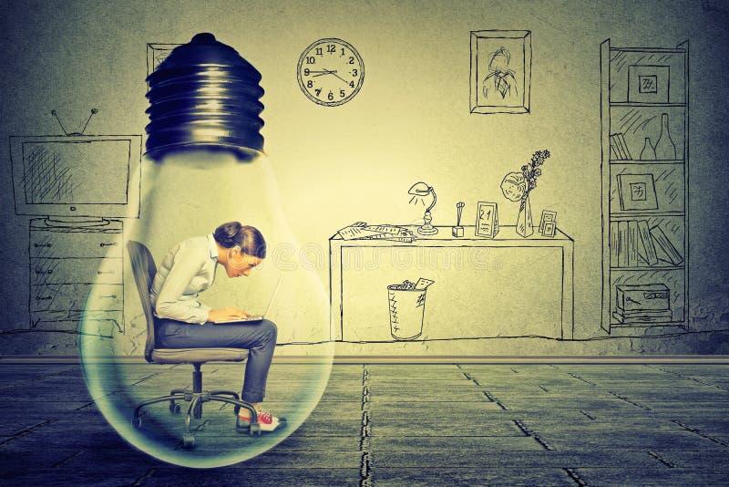 Junge Frau des Seitenprofils, die das Arbeiten an dem Computer sitzt innerhalb der elektrischen Lampe verwendet lizenzfreies stockfoto