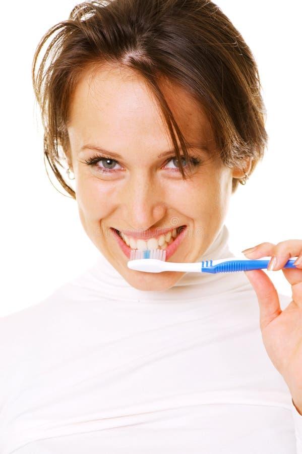 Junge Frau des smiley, die ihre Zähne säubert lizenzfreie stockbilder