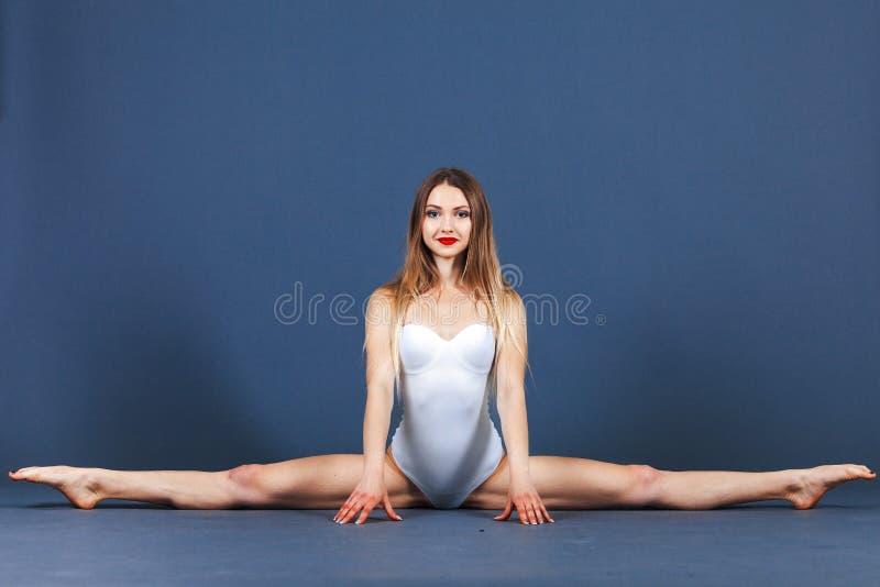 Junge Frau des Sports in sportwear Bodysuit sitzt auf einer Schnur auf einem blauen Hintergrund Schönes Tanzen der jungen Frau de lizenzfreie stockfotos