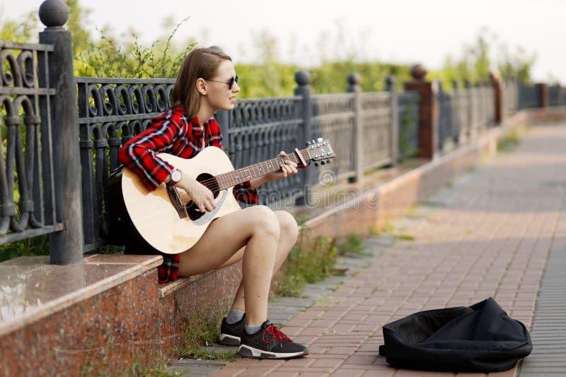 Junge Frau des Straßenmusikers, die Akustikgitarre spielt und in einem Stadtpark singt stockfoto