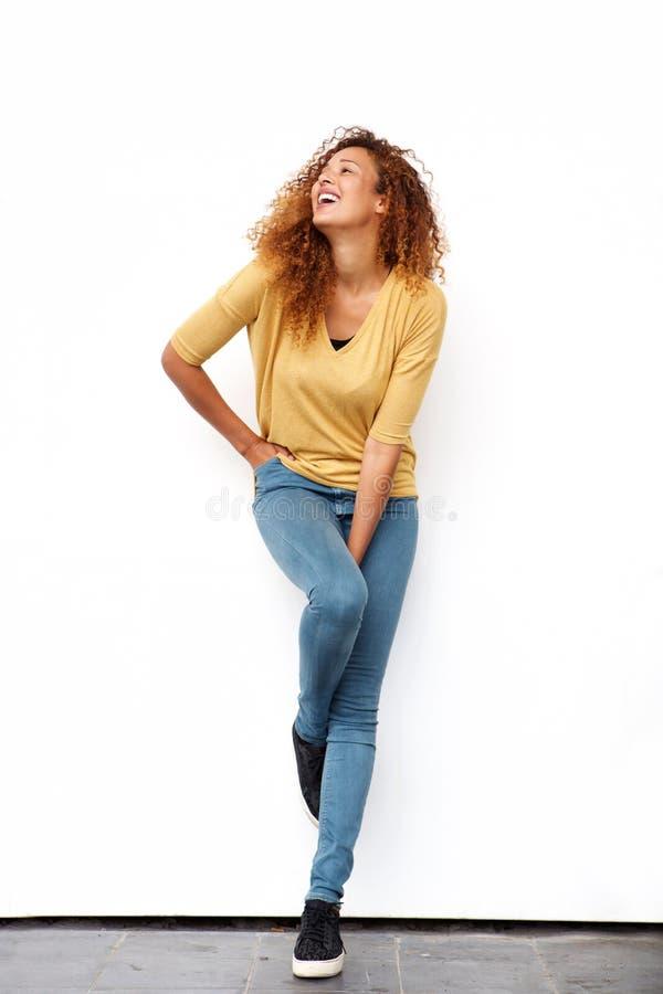 Junge Frau des vollen Körpers, die gegen weiße Wand lacht stockfoto