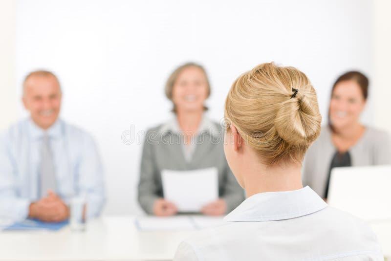 Junge Frau des Vorstellungsgesprächs mit Geschäftsteam stockfotografie