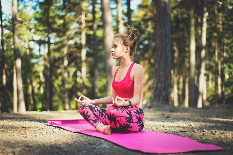 Junge Frau, die in übendem Yoga des Lotussitzes in einem Waldfreiheitskonzept meditiert Entspannen Sie sich, Sinnes- und Körpergl lizenzfreie stockfotos