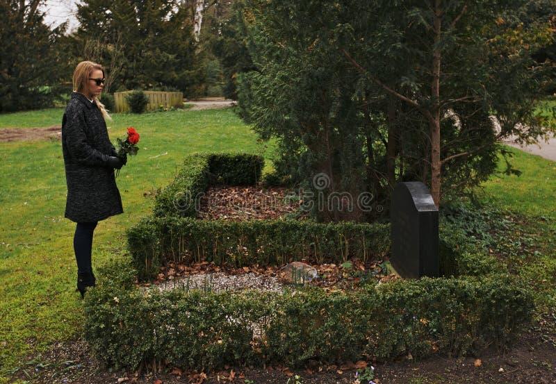Junge Frau, die über den Kirchhof hält Blumen sich Sorgen macht stockfotografie