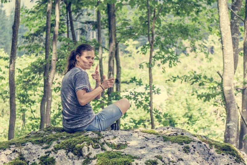 Junge Frau, die über ihrer Schulter auf einem Waldfelsen schaut stockbilder
