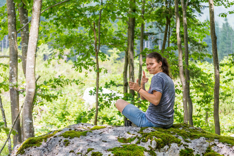 Junge Frau, die über ihrer Schulter auf einem Waldfelsen schaut lizenzfreies stockbild