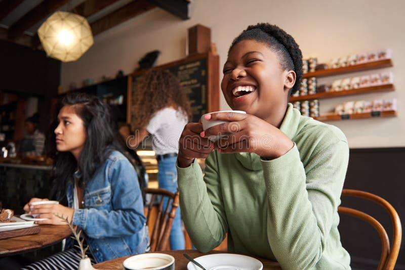Junge Frau, die über Kaffee mit Freunden in einem Café lacht lizenzfreies stockbild