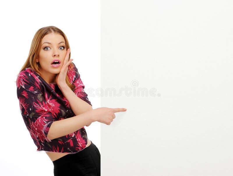Junge Frau, die über Rand des Leerzeichens späht lizenzfreie stockbilder