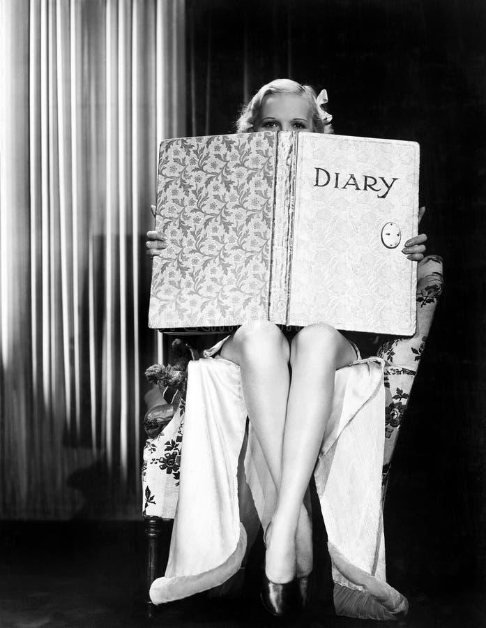 Junge Frau, die über Spitze eines übergroßen Buches schaut (alle dargestellten Personen sind nicht längeres lebendes und kein Zus stockfotografie